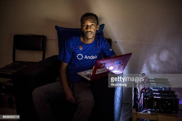 Eugene Mutai bitcoin 'miner' and software developer poses for a photograph with cryptocurrency 'mining' machines at his home in Nairobi Kenya on...