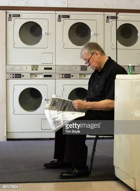 Eugene Szykowny reads a newspaper as he awaits his laundry near a bank of commercial Maytag clothes dryers at a laundromat June 22 2005 in Glenview...