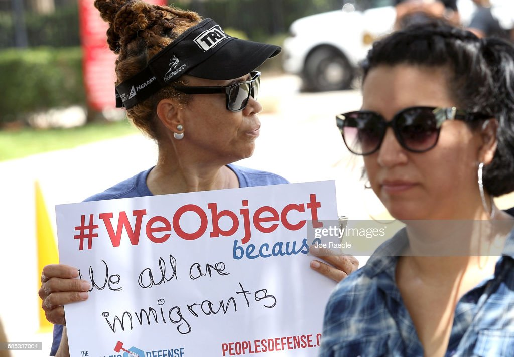Eugenia Caballero (L) and Maria Alvarez take part in a protest in front of the United States Citizenship and Immigration Services building on May 19, 2017 in Miramar, Florida. The protesters are asking for the Trump Administration to stop the numerous arrests of undocumented immigrants that they say have become too frequent during court appearances and when people show up to immigration offices to renew temporary permits.
