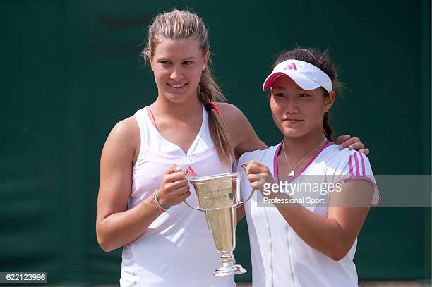 Eugenie Bouchard of Canada and Grace Min of the USA hold the trophy after winning the girls' doubles final against Demi Schuurs of the Netherlands...