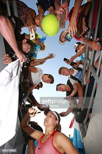 Eugenie Bouchard of Canada signs autographs for supporters in the crowd as she leaves the court after winning her first round match against...