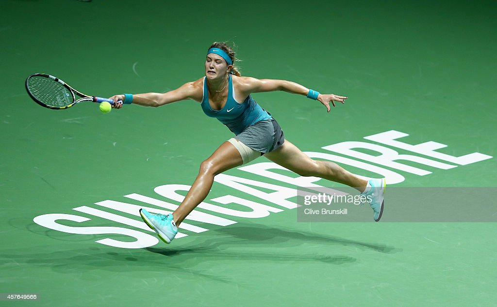 Eugenie Bouchard of Canada stretches to play a forehand against Ana Ivanovic of Serbia in their round robin match during the BNP Paribas WTA Finals at Singapore Sports Hub on October 22, 2014 in Singapore.