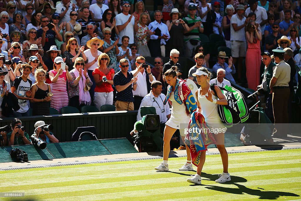 Eugenie Bouchard of Canada waves to the fans as she walks off with Simona Halep of Romania after their Ladies' Singles semi-final match on day ten of the Wimbledon Lawn Tennis Championships at the All England Lawn Tennis and Croquet Club on July 3, 2014 in London, England.