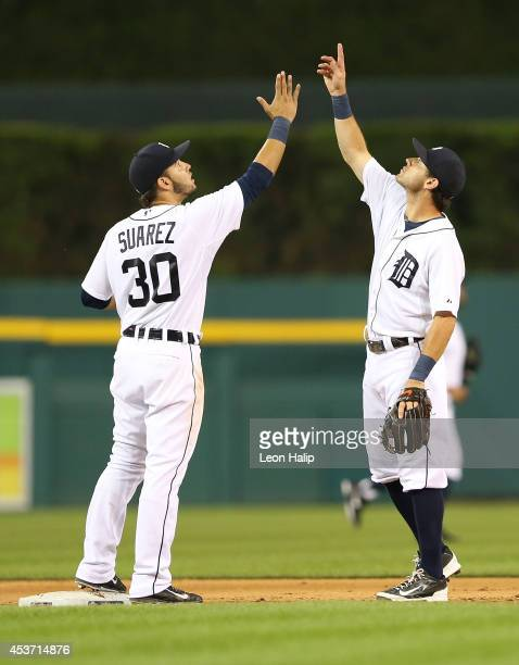 Eugenio Suarez and Ian Kinsler of the Detroit Tigers celebrate a win over the Seattle Mariners at Comerica Park on August 16 2014 in Detroit Michigan...