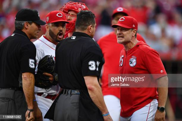 Eugenio Suarez of the Cincinnati Reds and Manager David Bell of the Cincinnati Reds argue with home plate umpire Carlos Torres after the first inning...