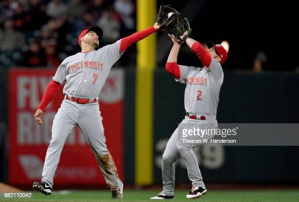 Eugenio Suarez of the Cincinnati Reds catches a popup off the bat of Joe Panik of the San Francisco Giants while avoiding a collision with teammate...