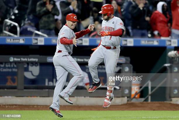 Eugenio Suarez of the Cincinnati Reds celebrates his solo home run with third base coach J.R. House in the sixth inning against the New York Mets at...