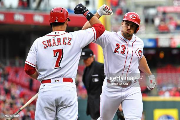 Eugenio Suarez of the Cincinnati Reds celebrates with Adam Duvall of the Cincinnati Reds after Duvall hit a home run in the first inning against the...