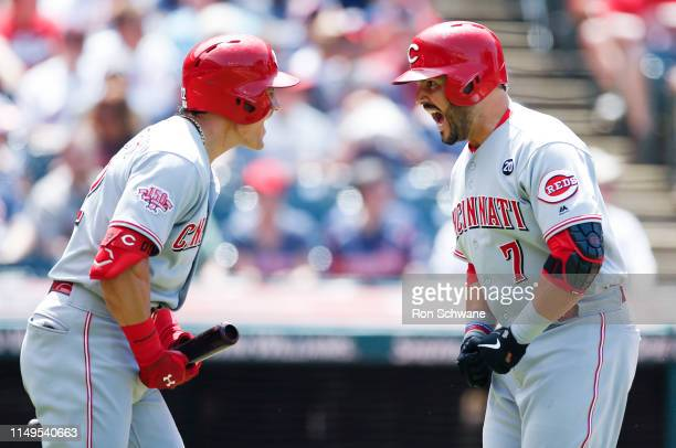 Eugenio Suarez of the Cincinnati Reds celebrates with Derek Dietrich after hitting a solo home run off Zach Plesac of the Cleveland Indians during...