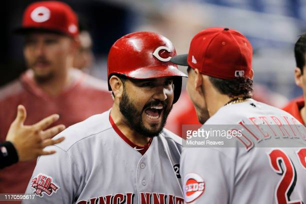 Eugenio Suarez of the Cincinnati Reds celebrates with Derek Dietrich after hitting a two-run home run during the first inning against the Miami...