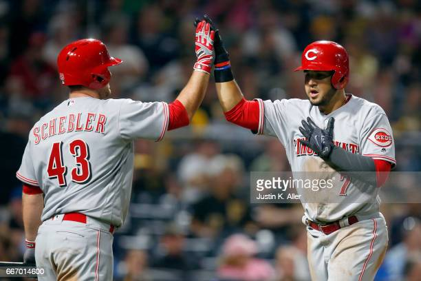 Eugenio Suarez of the Cincinnati Reds celebrates with Scott Schebler after hitting a home run in the fifth inning against the Pittsburgh Pirates at...