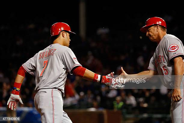 Eugenio Suarez of the Cincinnati Reds high fives third base coach Jim Riggleman after hitting a two run home run against the Chicago Cubs during the...