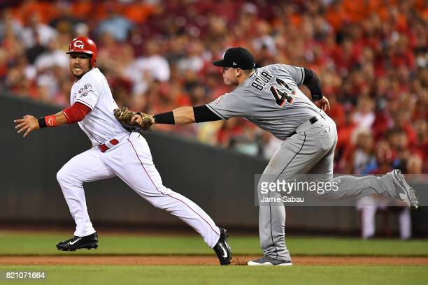 Eugenio Suarez of the Cincinnati Reds is picked off trying to steal second base by Justin Bour of the Miami Marlins in the fourth inning at Great...