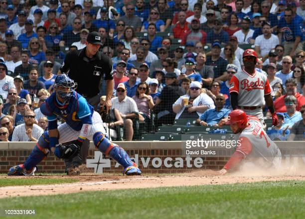 Eugenio Suarez of the Cincinnati Reds is safe at home plate as Willson Contreras of the Chicago Cubs waits for the throw during the fourth inning on...