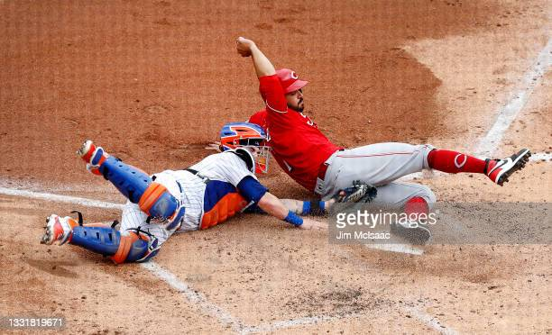 Eugenio Suarez of the Cincinnati Reds is tagged out at the plate by Tomas Nido of the New York Mets during the third inning at Citi Field on August...