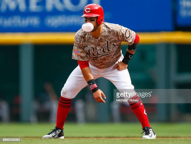 Eugenio Suarez of the Cincinnati Reds leads off at first base while blowing a bubble during the second inning against the Colorado Rockies at Great...
