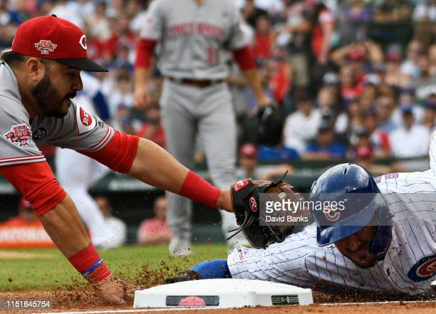 Eugenio Suarez of the Cincinnati Reds tags out Kris Bryant of the Chicago Cubs at third base during the first inning at Wrigley Field on May 25, 2019...