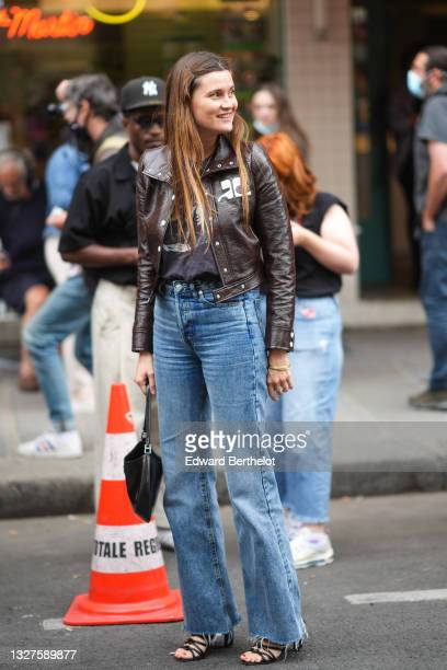 Eugénie Trochu wears a black with gray picturd t-shirt, a black shiny leather biker jacket from Carhartt, blue faded denim ripped jeans flared pants,...