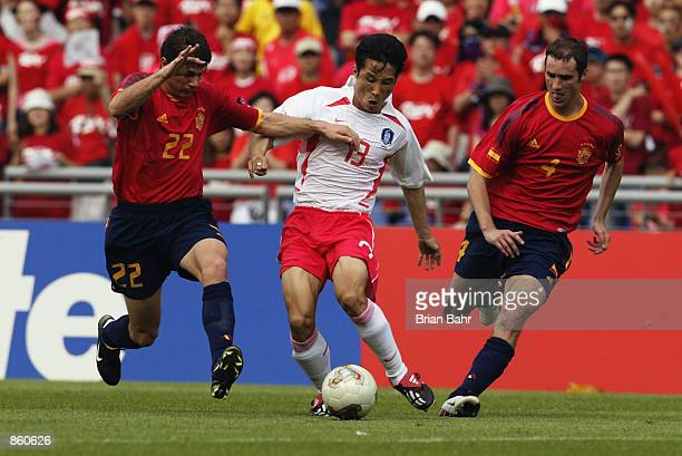 Eul Yong Lee of South Korea takes the ball between Joaquin and Ivan Helguera of Spain during the FIFA World Cup Finals 2002 Quarter Finals match...