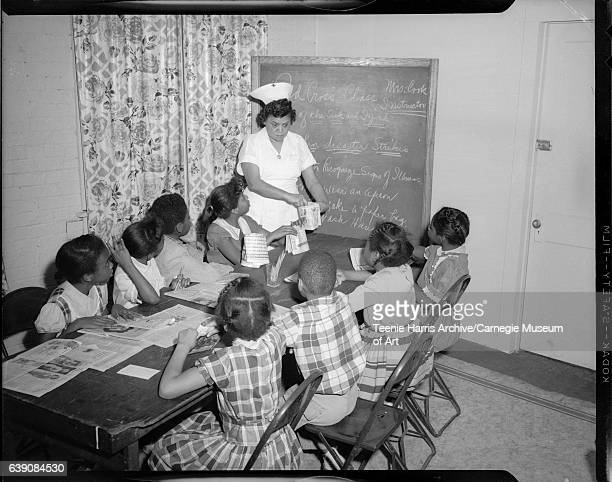 Eunice Cook wearing nursing uniform with cross on hat and circular brooch at collar holding folded newspaper standing at end of table with two boys...