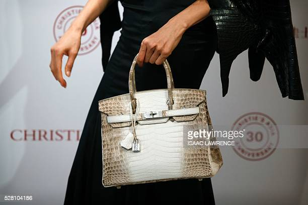 Eunis Chan models a Matte White Himalaya Niloticus Crocodile Diamond Birkin with 18K gold and diamond hardware one of the most valuable handbags in...
