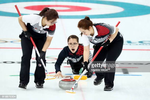 EunJung Kim of Republic of Korea delivers a stone between YeongMi Kim and SeonYeong Kim during their game against Switzerland in the Curling Women's...