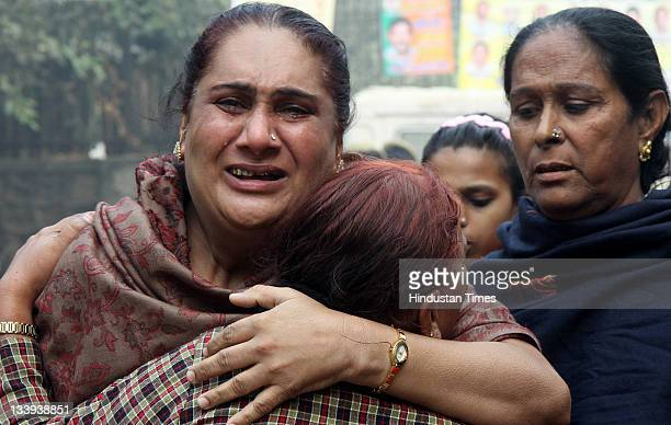 A eunuch is comforted as she mourns for a friend at the scene of Sunday's fire at Nand Nagari Community Centre on November 21 2011 in East Delhi...