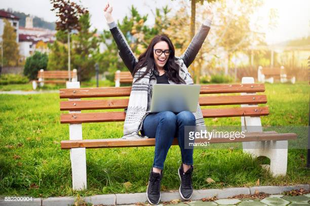 euphoric winner watching a laptop - achievement stock pictures, royalty-free photos & images