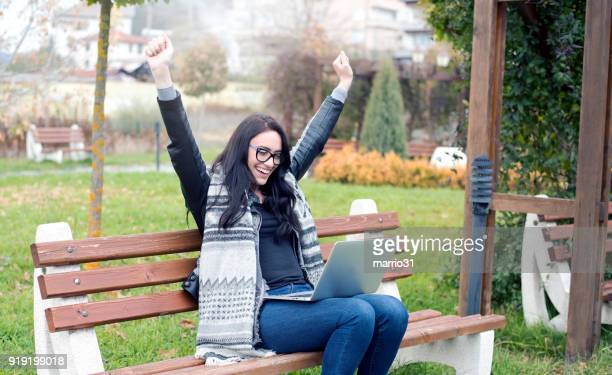 euphoric winner watching a laptop - bid stock pictures, royalty-free photos & images
