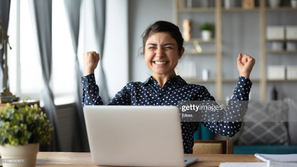 Euphoric young indian girl celebrate online victory triumph with laptop : Stock Photo