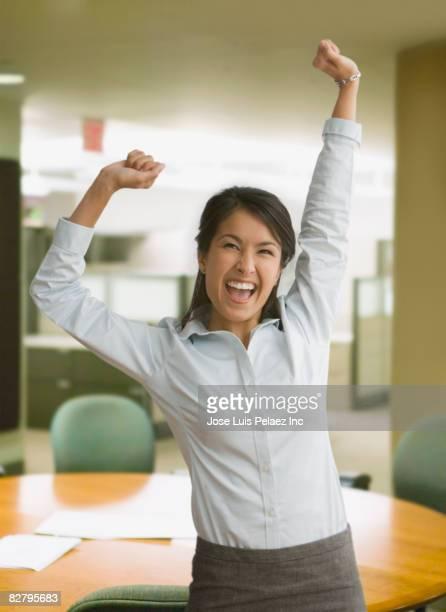 Eurasian businesswoman celebrating in office