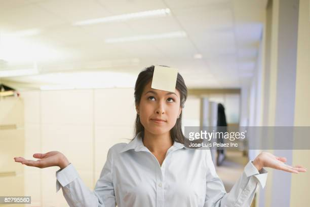 Eurasian businesswoman gesturing with sticky note on forehead
