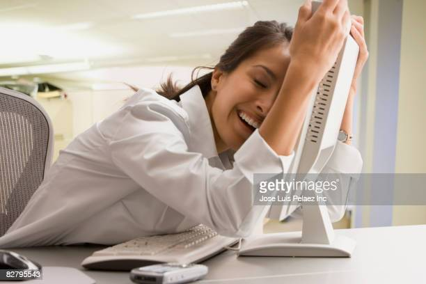 Eurasian businesswoman hugging computer