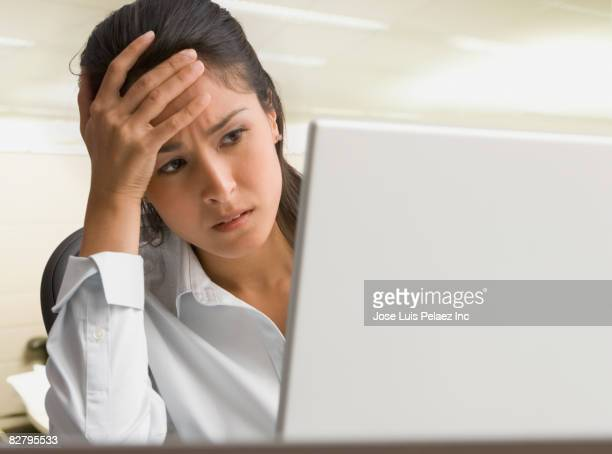 Eurasian businesswoman on laptop looking worried