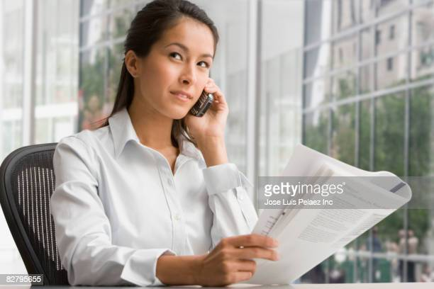 Eurasian businesswoman with newspaper talking on cell phone