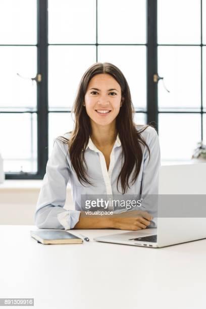 Eurasian Female Business Leader Sitting at Her Desk