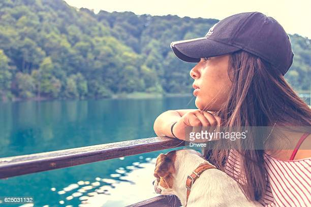 Eurasian Girl And Dog Sitting On Boat Side View Contemplating Nature