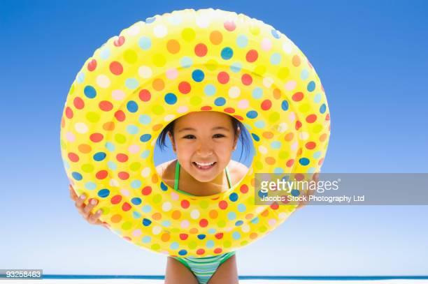 Eurasian girl holding inflatable ring on beach