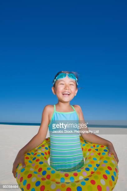 Eurasian girl in inflatable ring on beach