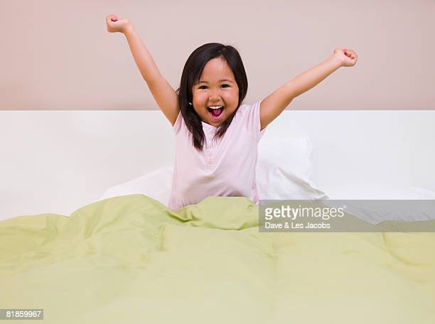 Eurasian girl stretching in bed