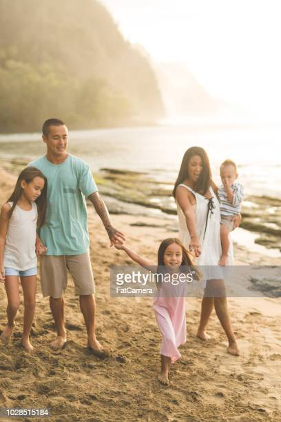 Papa et maman eurasienne marcher le long de la plage avec leurs trois enfants