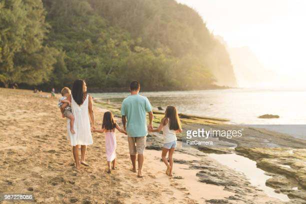 eurasian mom and dad walk along the beach with their three children - kauai stock pictures, royalty-free photos & images