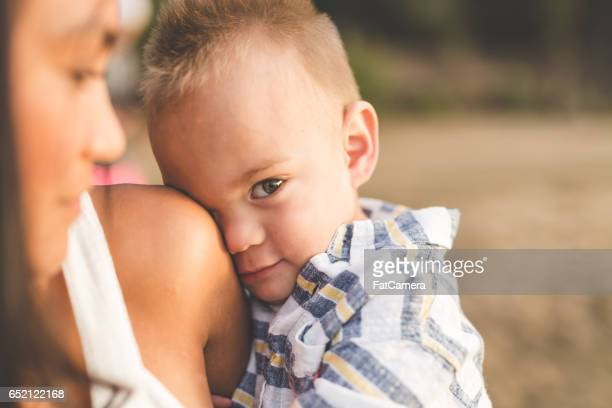 Eurasian mother holding adorable son along sandy Hawaii beach