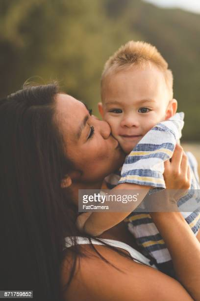 Eurasian mother holding adorable son along sandy Hawaii beach