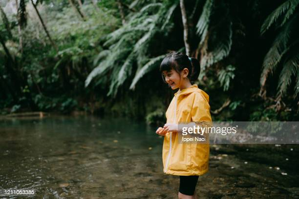 eurasian preschool girl smiling in rainforest, okinawa, japan - reality fernsehen stock pictures, royalty-free photos & images