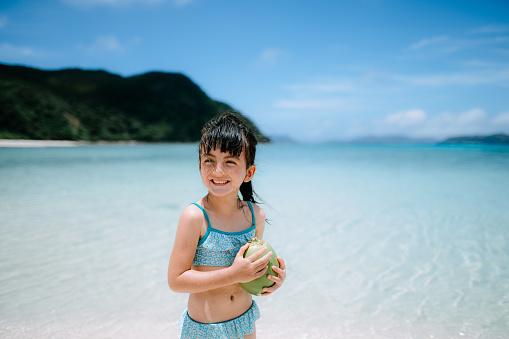 Eurasian preschool girl smiling with coconut on tropical beach, Okinawa, Japan - gettyimageskorea