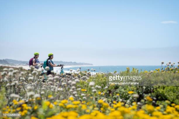 eurasian sisters with bicycles enjoying ocean view from wildflower bluff - san mateo county stock pictures, royalty-free photos & images