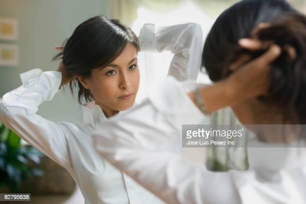 Eurasian woman fixing hair in mirror