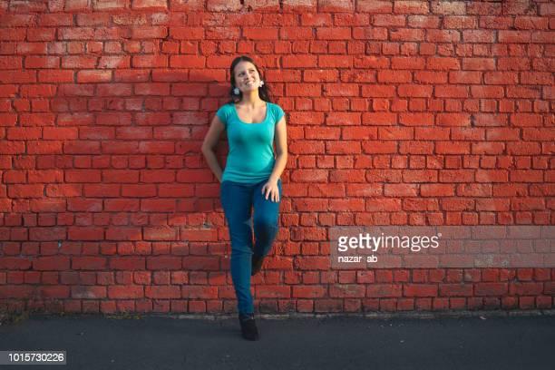 Eurasian woman posing against brick wall.