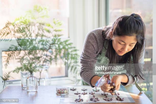 eurasian young woman making chocolate christmas trees in sunlit kitchen - hygge stock pictures, royalty-free photos & images